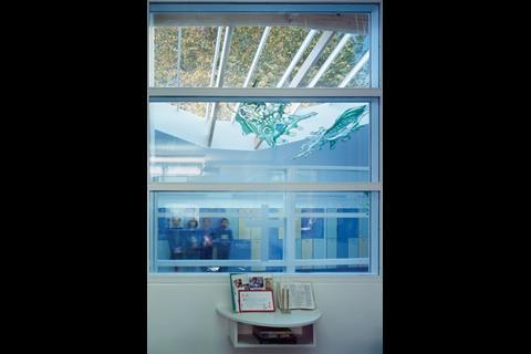 A glass partition at the rear of each classroom channels in daylight and offers views through the school and out to the central tree. The vivid mobile sculpture was largely created by the pupils